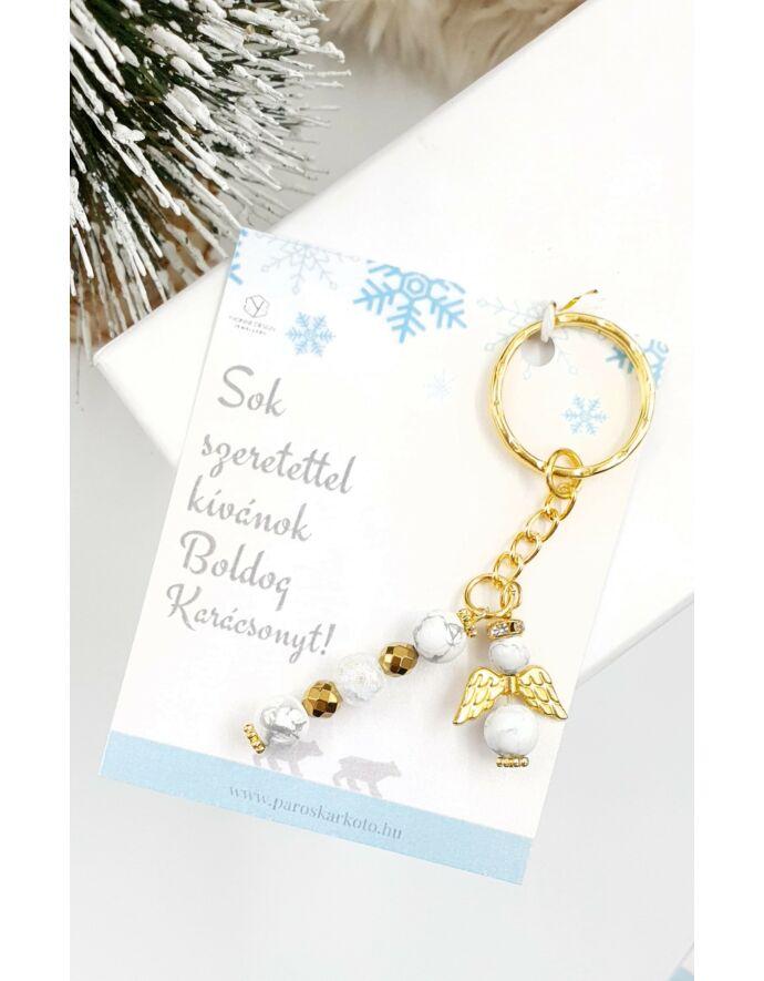 Aranyszín kulcstartó angyalka medállal.  Az ajándékszett része a kulcstartó, az üzenetkártya, és egy fehér tüll tasak!